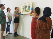Students in ART 496 hanging an artwork